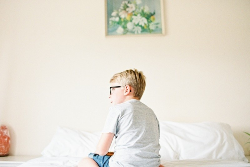 son alone on bed in front of flowered framed art by photographer kjrsten madsen