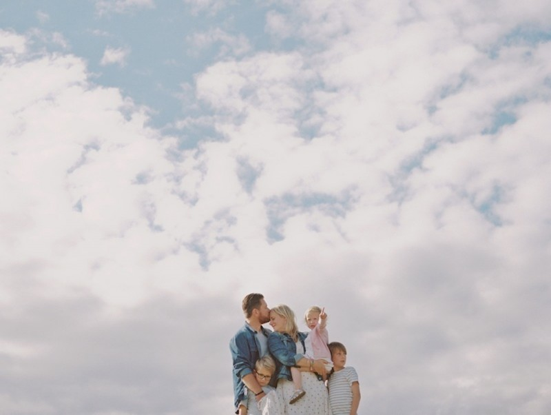 whole family against blue sky negative space photo by kjrsten madsen