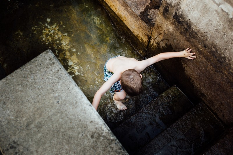 12 Boy walks up concrete stairs out of water by Darcy Troutman Photography