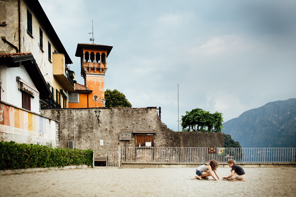 14 Children play in sand underneath a tower in Italy by Darcy Troutman Photography