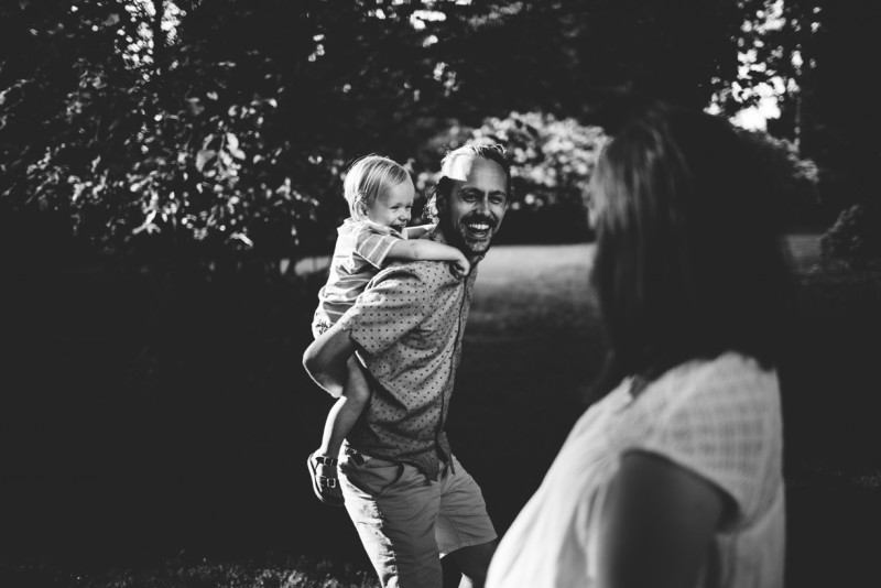 picture of father laughing giving child piggy back ride mother watching black and white by Dannie Melissa Wit Abeille Photography