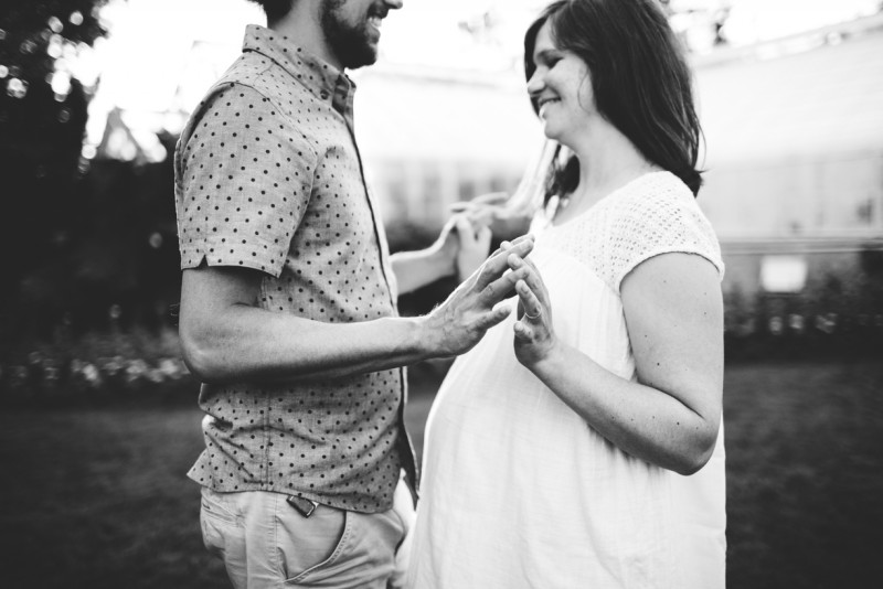 picture of husband and pregnant wife touching hands smiling black and white by Dannie Melissa Wit Abeille Photography