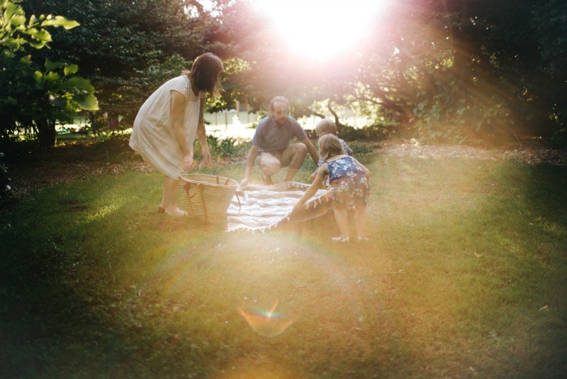 picture of family of four spreading out blanket for picnic by Dannie Melissa Wit Abeille Photography