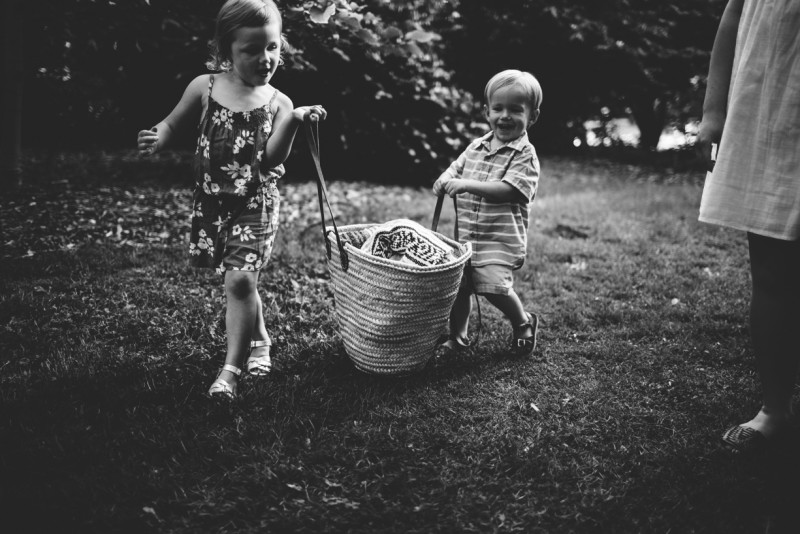 photo of brother sister carrying bag together black and white by Dannie Melissa Wit Abeille Photography