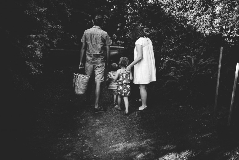 image of family of four walking down path from behind black and white by Dannie Melissa Wit Abeille Photography