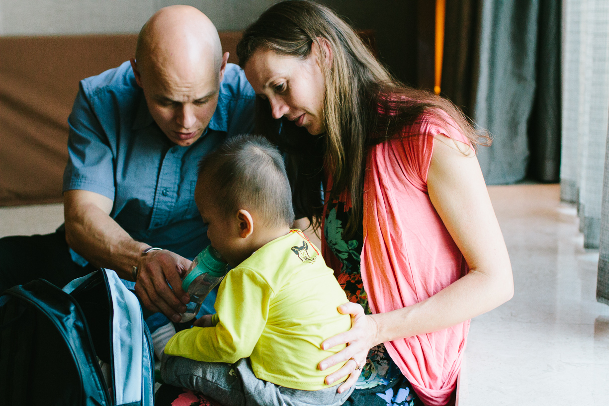 a picture of parents feeding their recently adopted son by christine keegan of china