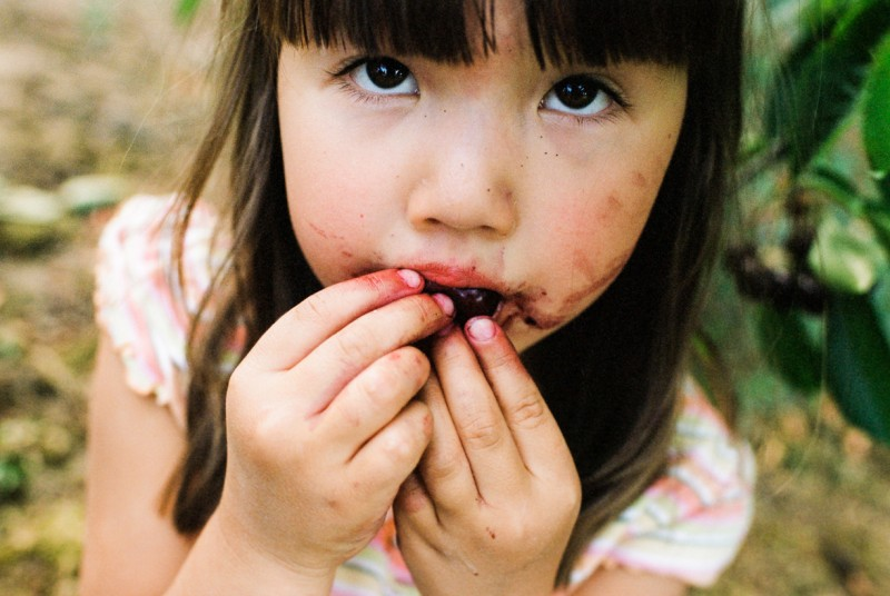 photo of young girl close up eating cherry messy by emily mccann