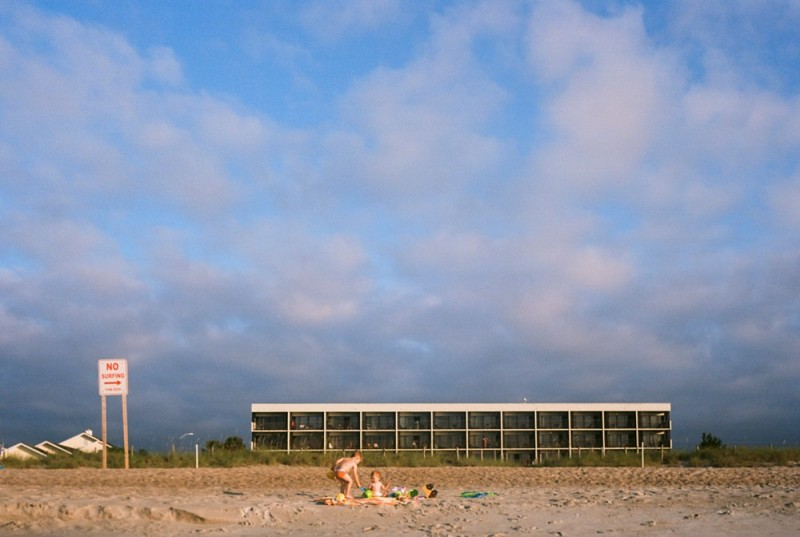 family on beach by motel film photo by jess rotenberg