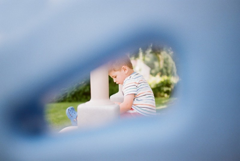 little boy on porch shot through photo by jeff rotenberg
