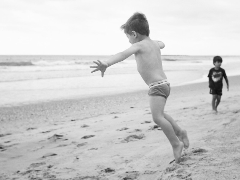 little boy on sand running around photo in black and white film by jess rotenberg