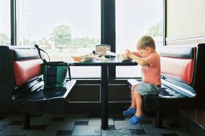 little boy sitting at fast food booth spilling photo by jess rotenberg