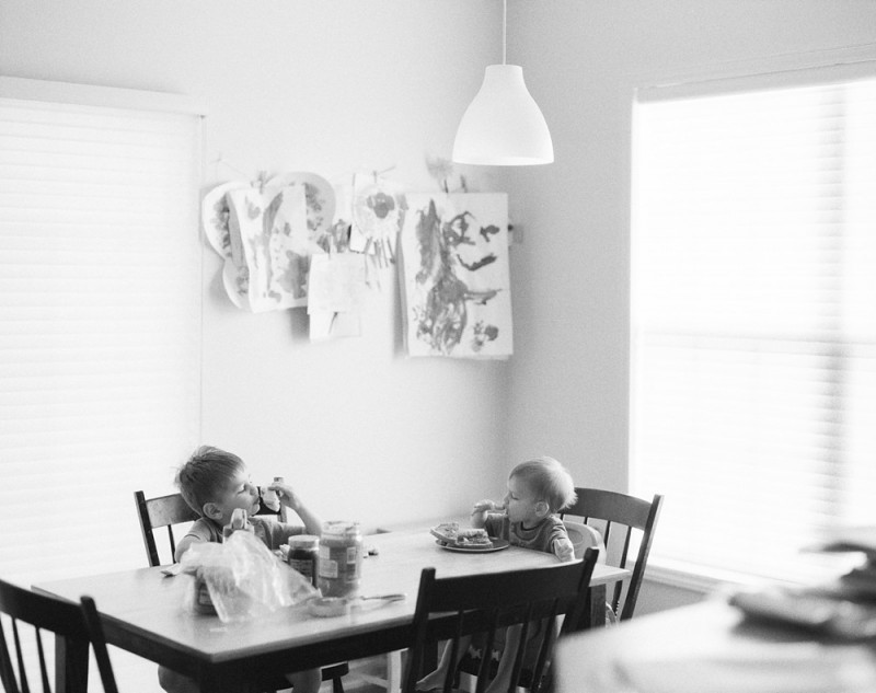 two brothers eating at table in black and white photo by jess rotenberg