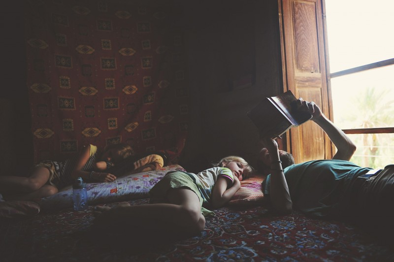 03_Family reads a book on the floor by Kirsty Larmour_Afternoon Stories_Garmeh_Iran