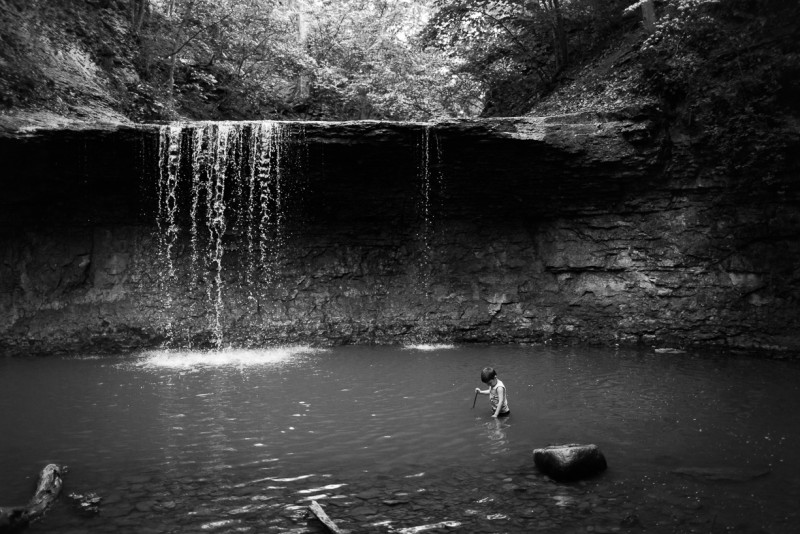 09_A child wades in a natural pool in front of a waterfall by Stephanie Jackson_The Deep End_Ohio