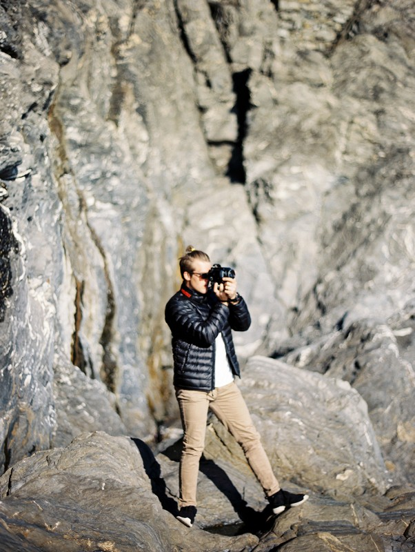 13 Photograph of man taking a picture amongst rocky cliffside By Jacquelyn Hayward