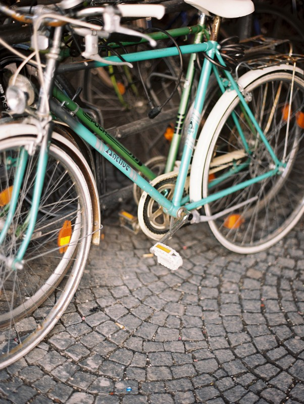 14 Vintage bikes parked on cobblestone street By Jacquelyn Hayward