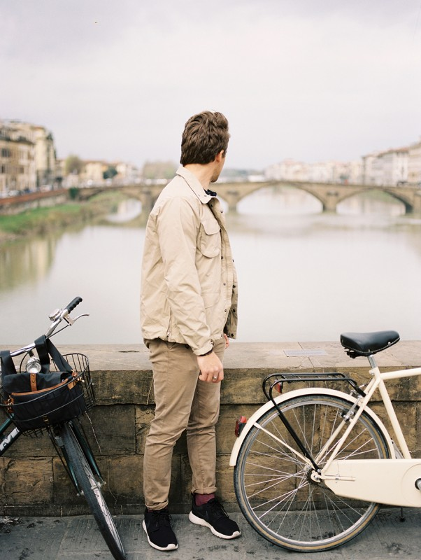 18 A man stands by bicycles and looks down a river toward a bridge By Jacquelyn Hayward