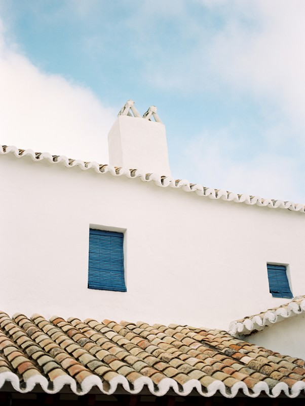 3 Blue shades in window of white building in Europe By Jacquelyn Hayward