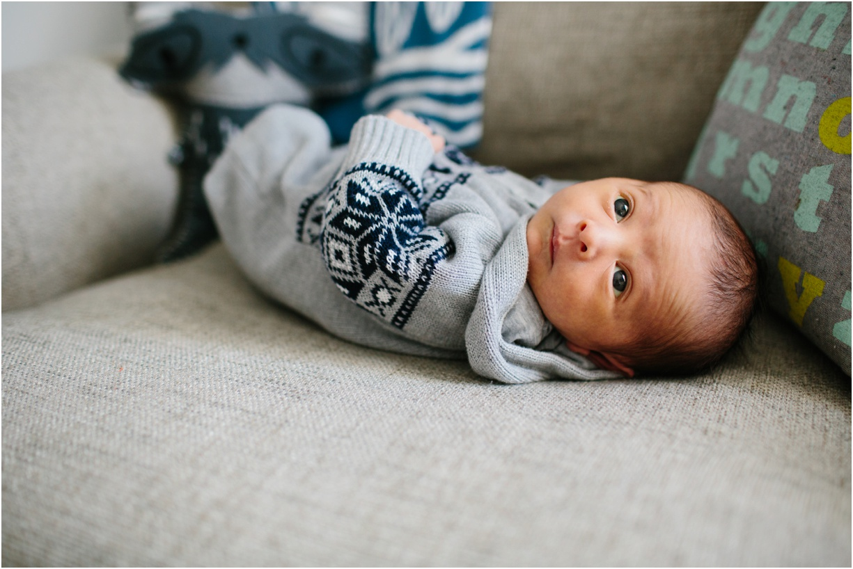a photo of an alert newborn laying on the couch by new york photographer mikki skinner