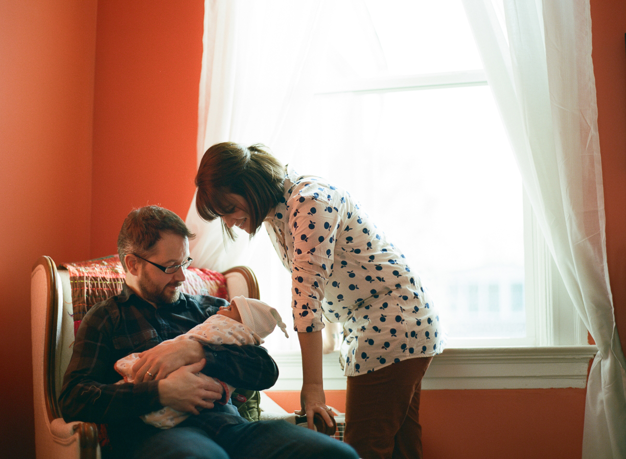 a picture of a family looking down lovingly at their newborn by St. Louis, Missouri photographer Shelly Goodman