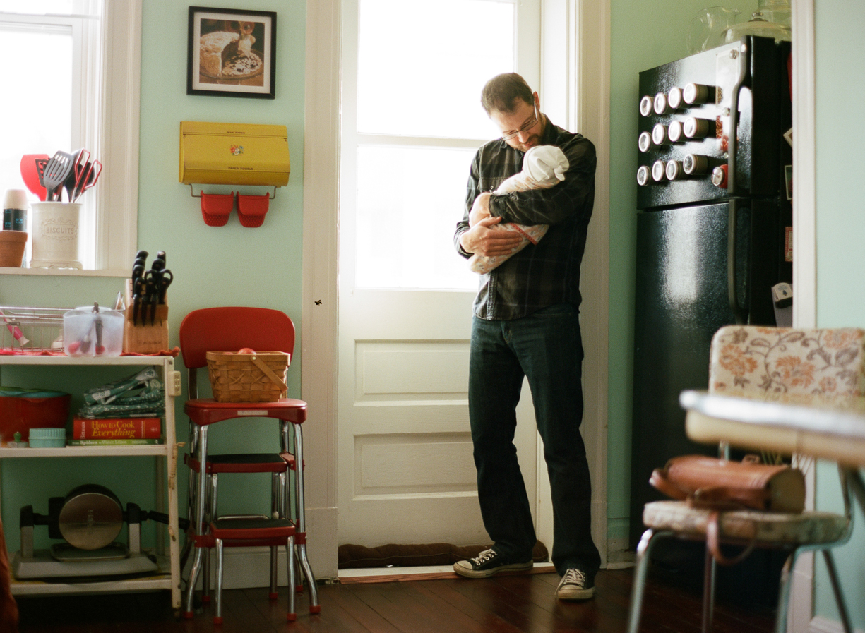 a picture of a father holding his newborn baby in the kitchen by photographer Shelly Goodman