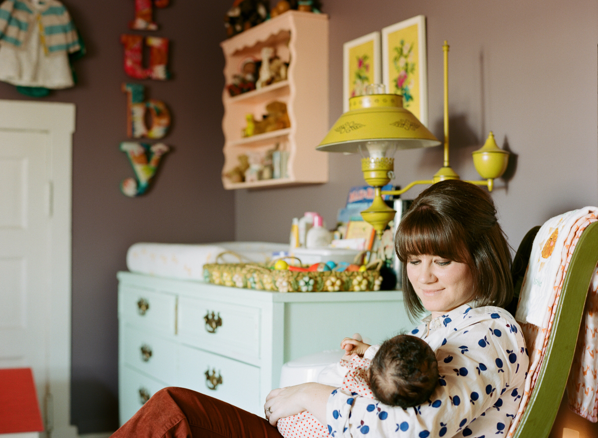 a picture of a mom rocking her adopted newborn baby in her nursery by photographer Shelly Goodman