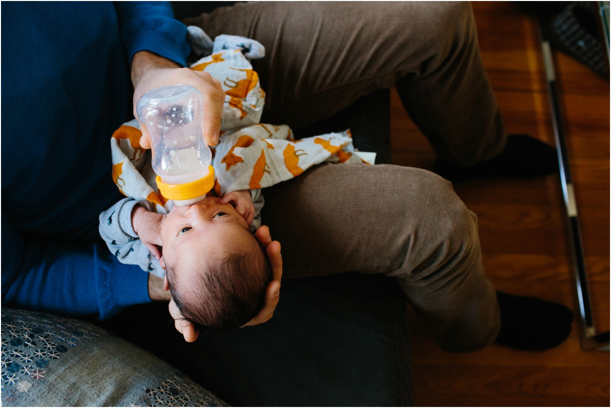 a picture of a newborn drinking his bottle by photographer mikki skinner of new york