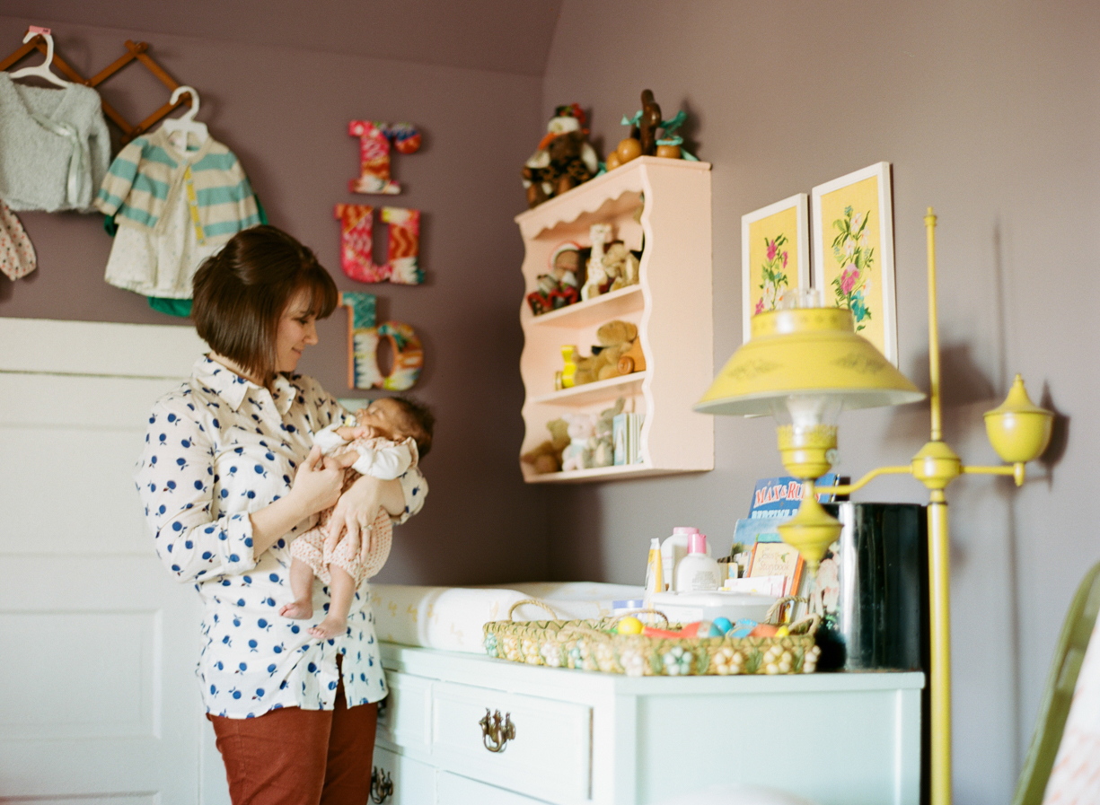 an image of a mother holding her newborn in her vintage styled nursery by photographer Shelly Goodman