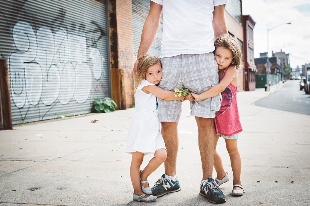 an image of two young girls holding father legs brooklyn new york by Keetch Miller