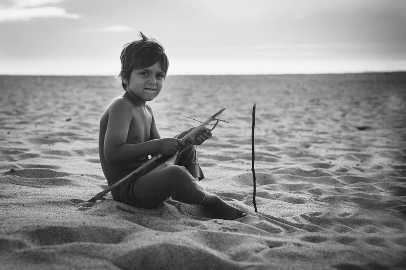 French boy playing with sticks in the sand by Nadia Stone