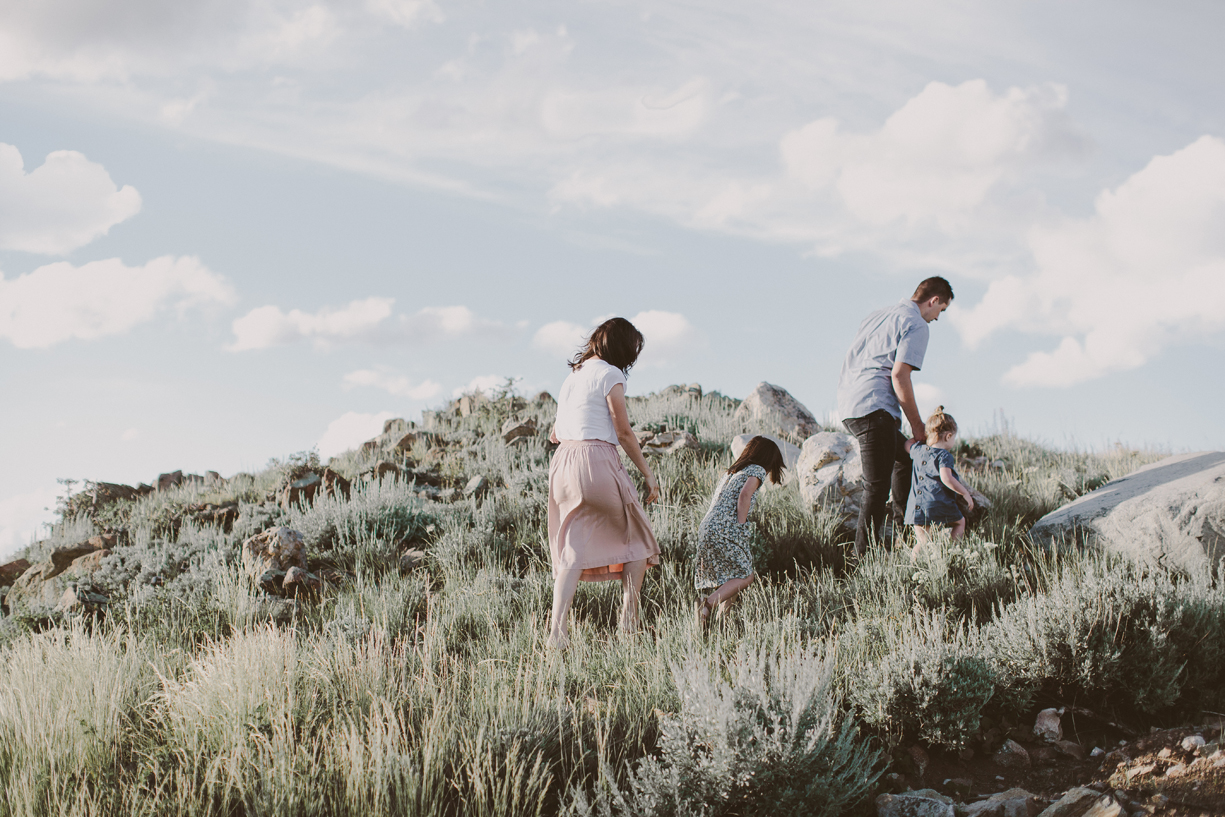 a photo of a family walking up a grassy hill by utah family photographer kandice breinholt