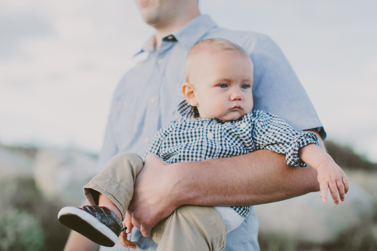 a photo of a father carrying his baby boy in his arms by utah photographer kandice breinholt