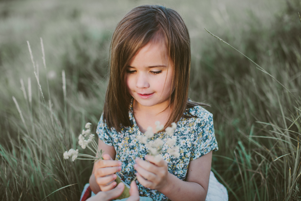 a picture of a young girl holding flowers in her hand by utah photographer kandice breinholt