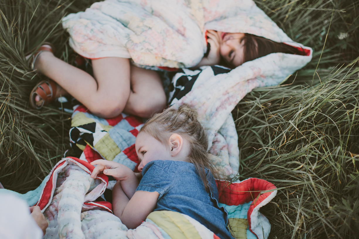 a picture of sisters snuggling on a quilt in the grass by utah photographer kandice breinholt