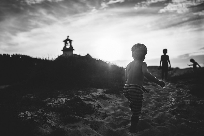 black and white backlit photo of boy running by Nadia Stone