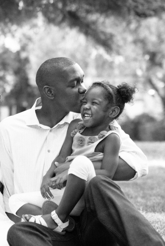black and white film photo of dad kissing his daughter by Samantha Kirk