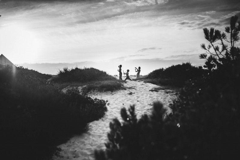 black and white photo of boys playing along a sand path in France by Nadia Stone