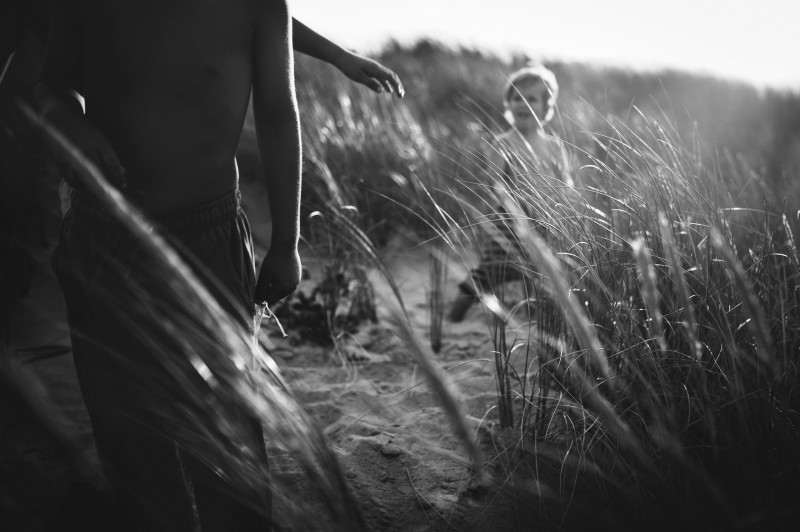 black and white picture of boys in tall grass by Nadia Stone
