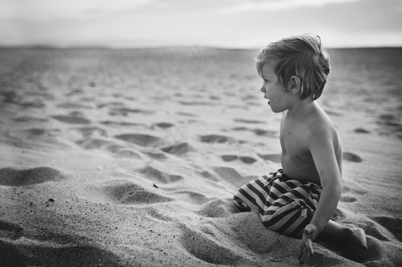 boy sitting in sand by Nadia Stone