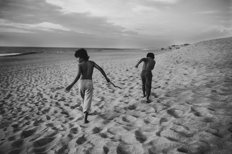boys walking along a sand dune in south France by Nadia Stone