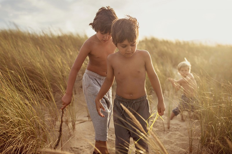 boys walking along a sand walkway in France by Nadia Stone