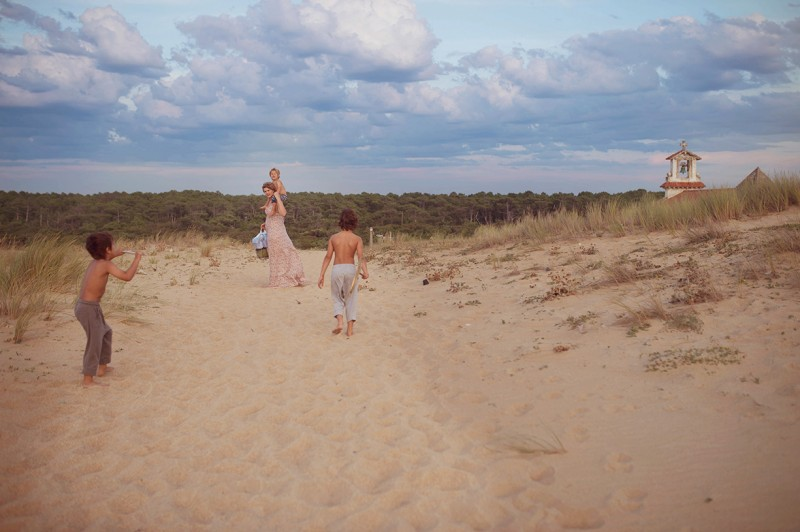 boys walking in the sand in France with their mom by Nadia Stone