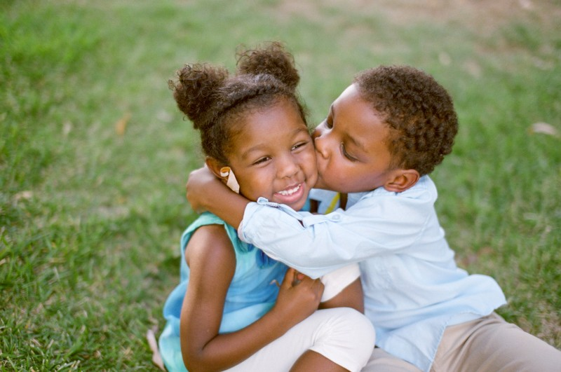 brother giving sister a kiss by Samantha Kirk