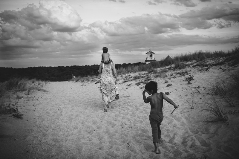 mother and boys walking along a sand dune by Nadia Stone