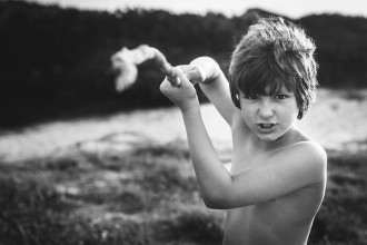 photo of boy playing with a stick by Nadia Stone