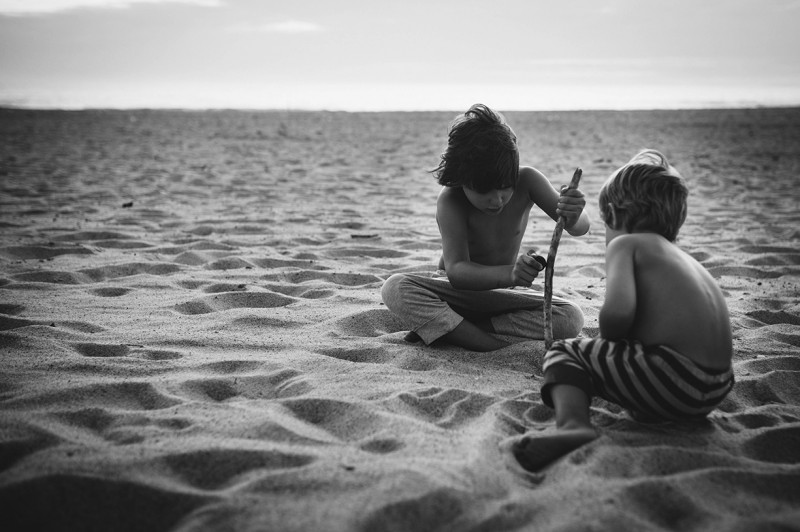 two boys playing in a sand dune in France by Nadia Stone