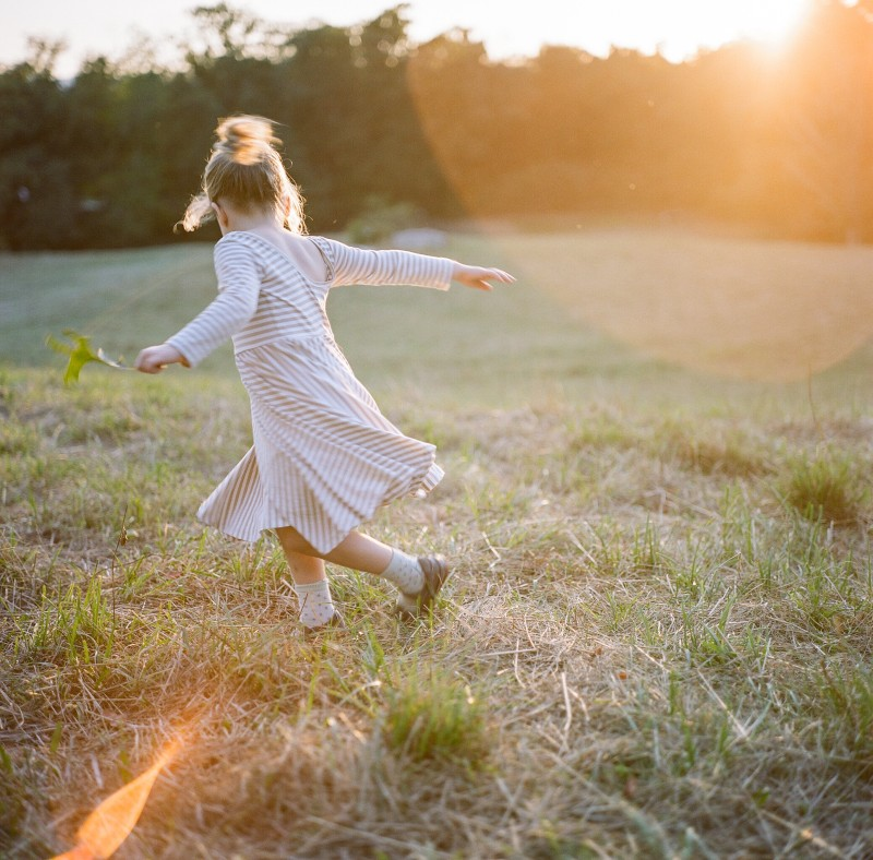 backlit photo with sunflare of girl running in a field by Elena Wolfe