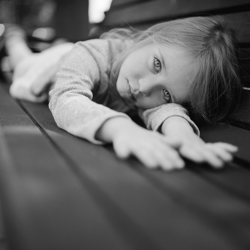 black and white film photo with a rolleiflex of girl laying on a bench by Elena Wolfe