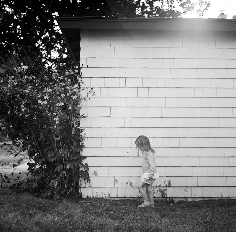 black and white picture of girl walking by a home by Elena Wolfe