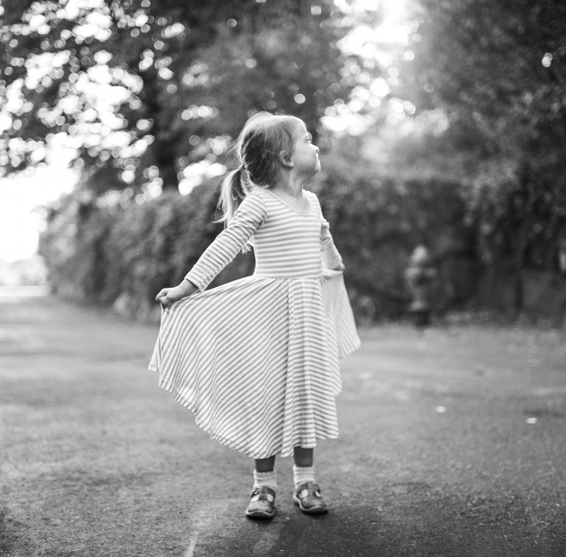 black and white square film pic of girl looking up and holding out her dress by Elena Wolfe